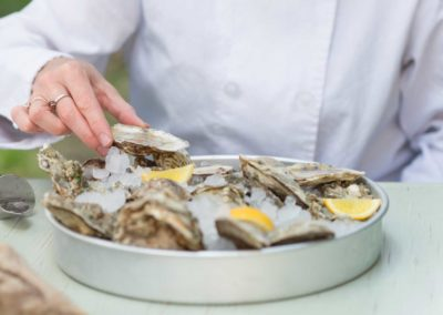 chef preparing raw oysters over ice with lemon wedges