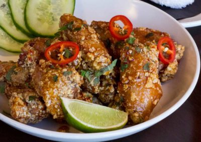 Vietnamese chicken wings with cucumber and lime wedge